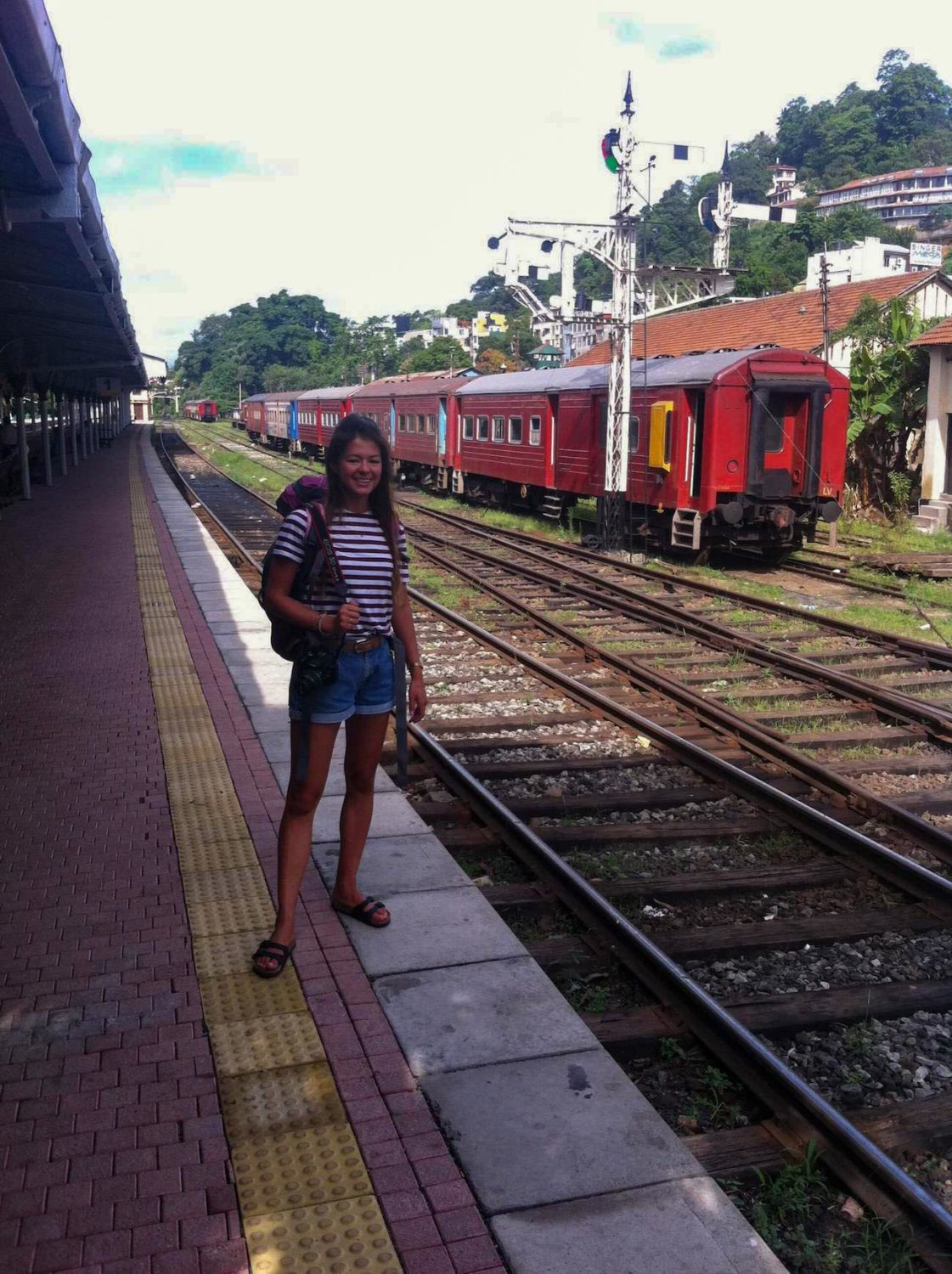 Kim waiting by a train station.
