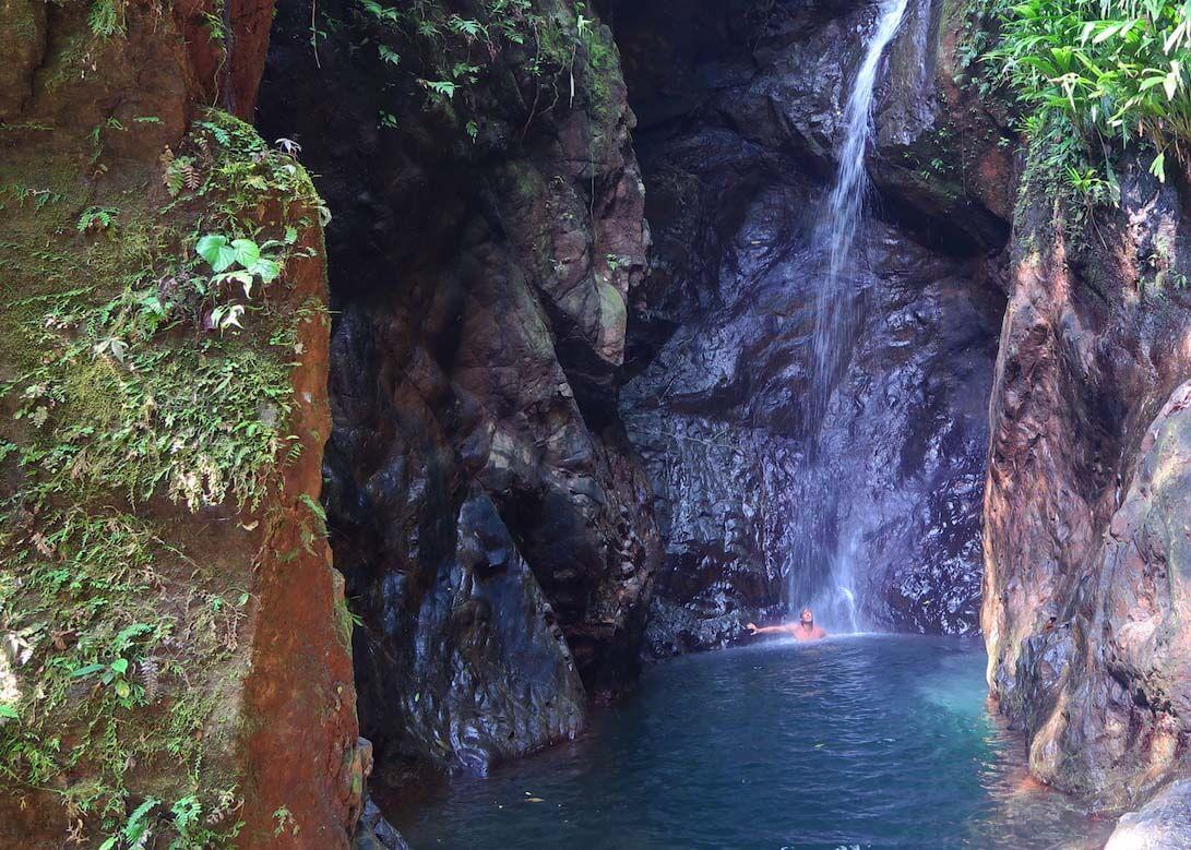 Chris bathing under Bahia Solano's Airport Waterfalls