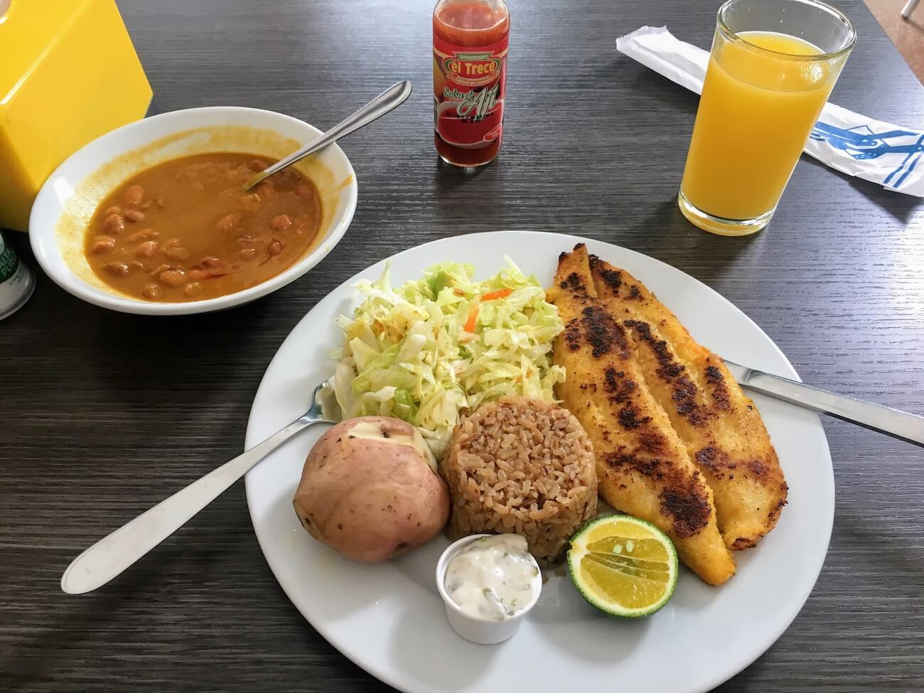 Close-up of Asteka restaurant fish lunch with soup and juice.