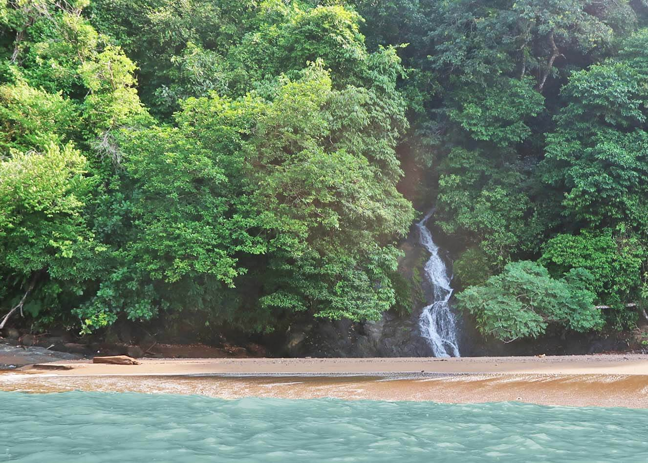 Cascada el Tigre peaking out from jungle and falling onto the beach