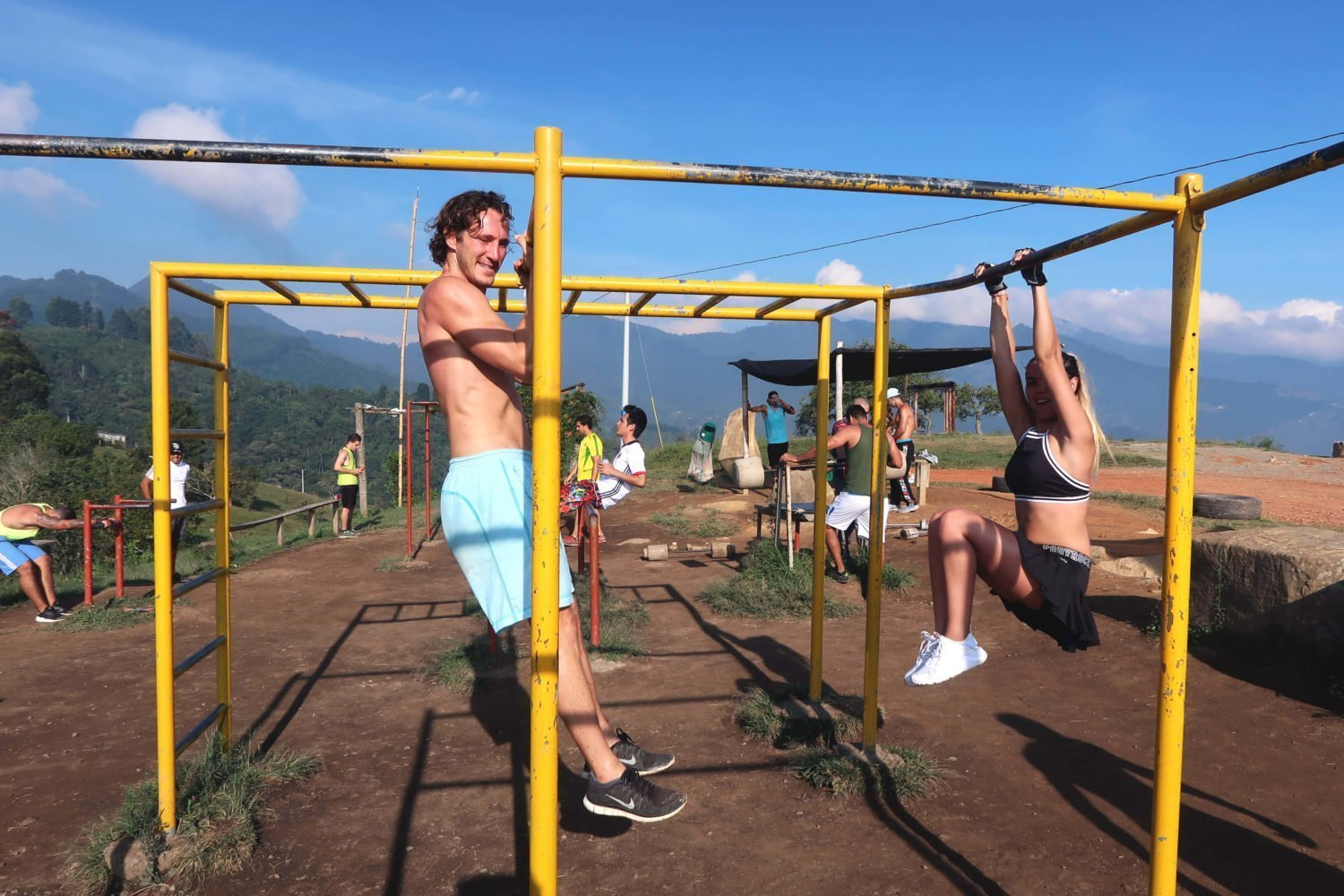 chris and juliana hanging on the bars at the outdoor gym at the top of cerro las tres cruces