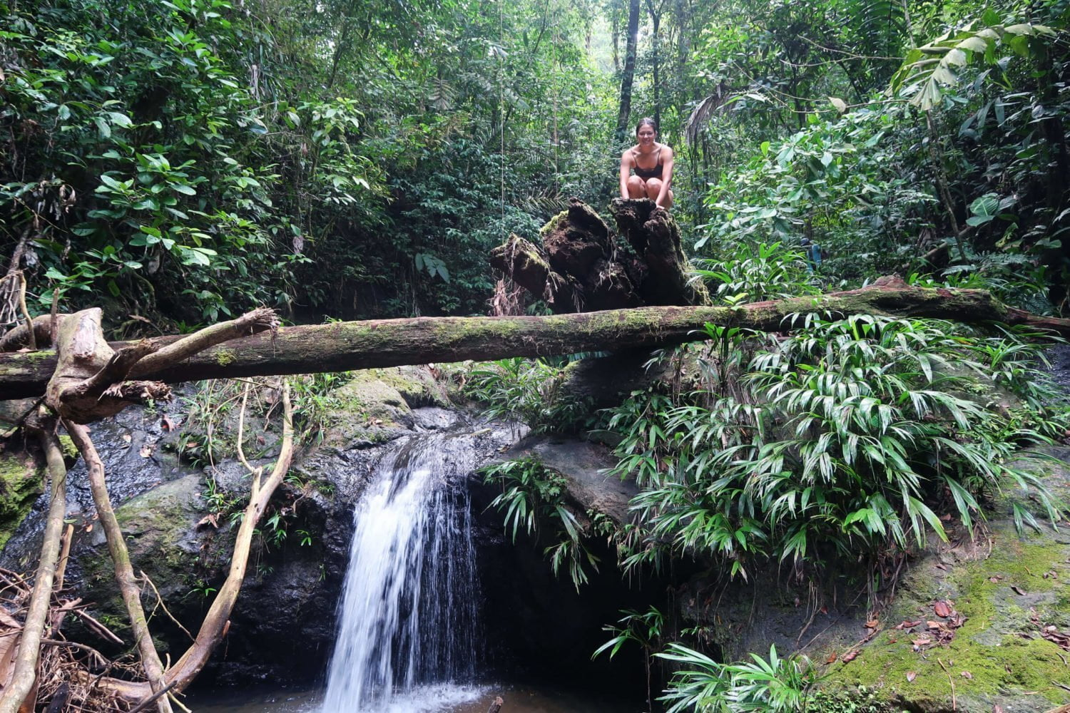 kim crouching on top one of many waterfalls at cascadas el tigre waterfalls in el valle