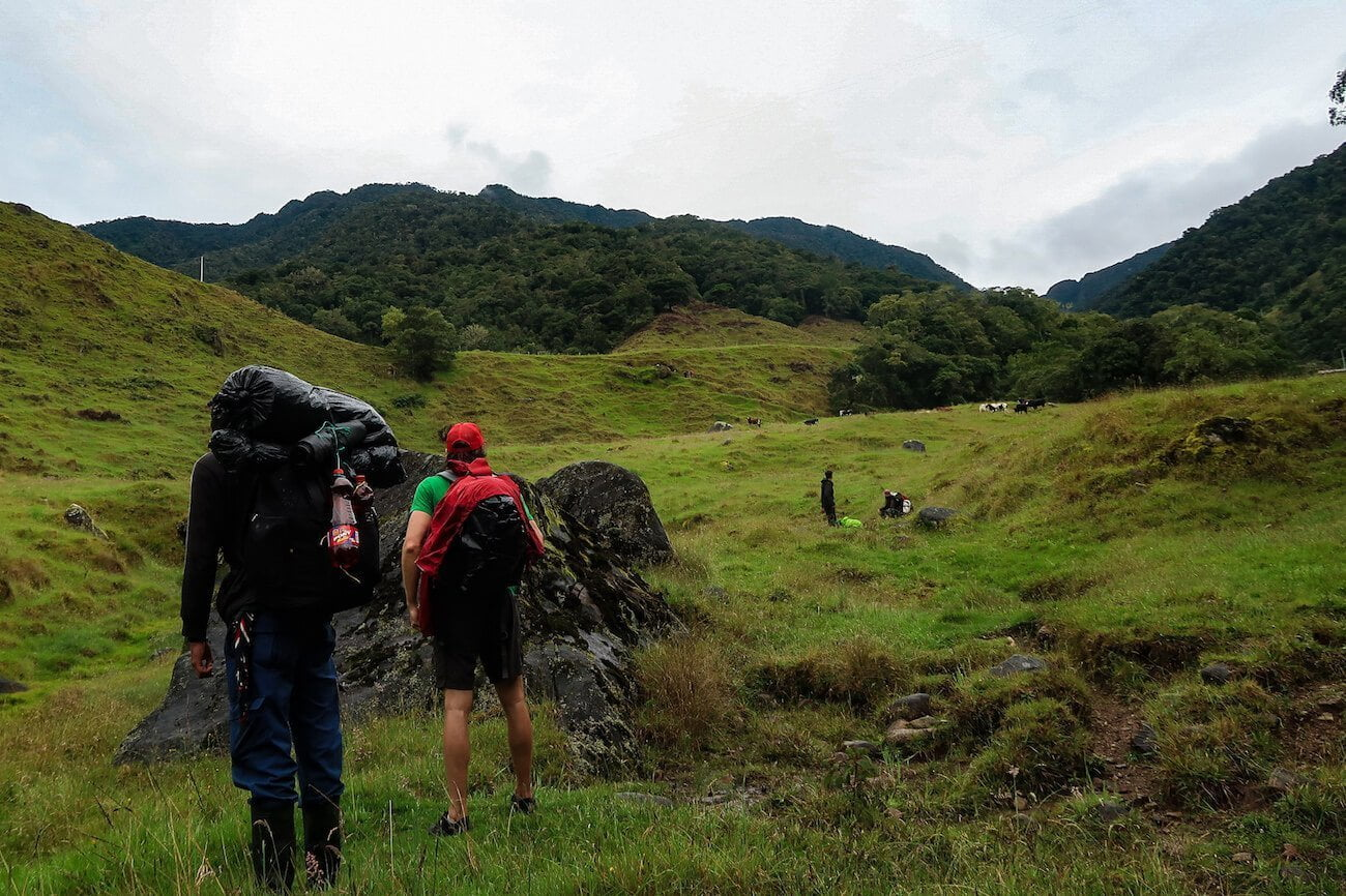 The group hiking along the green pasture.