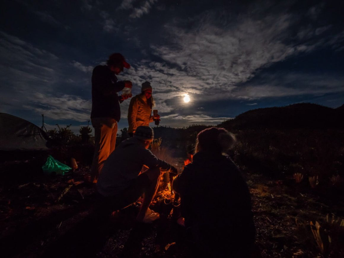 Huddled around campfire with moon behind us