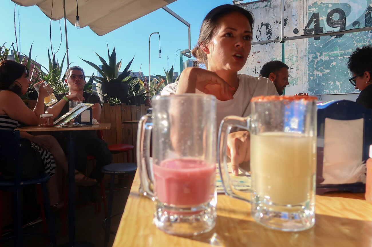 Close up of two jugs of pulque on rooftop with Kim talking in background
