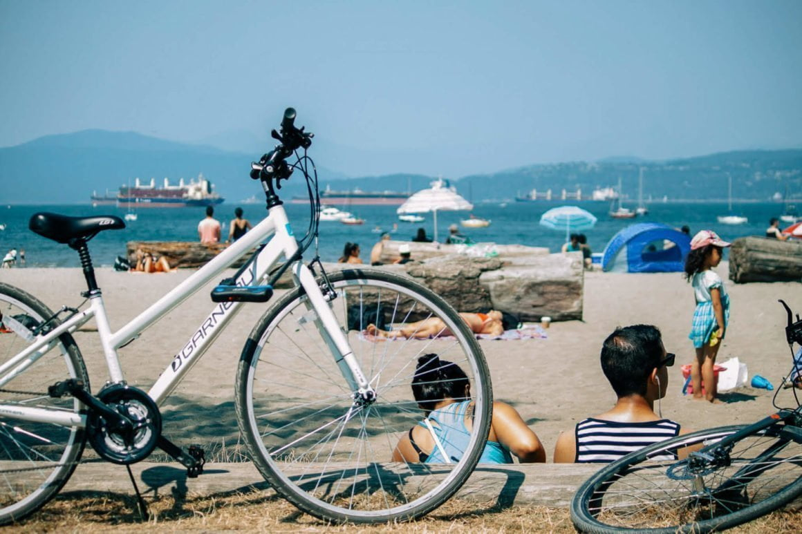 Kits beach vancouver with bike lying against a big log.