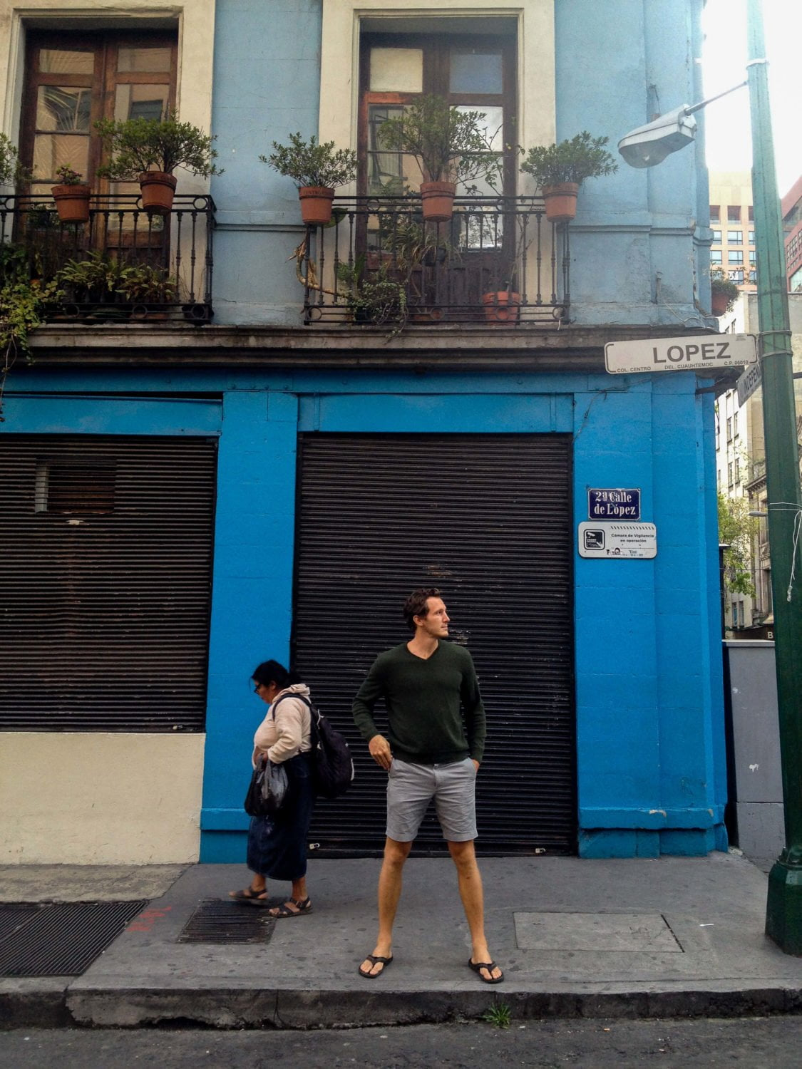 chris standing in front of blue building wearing shorts and sandals mexico city