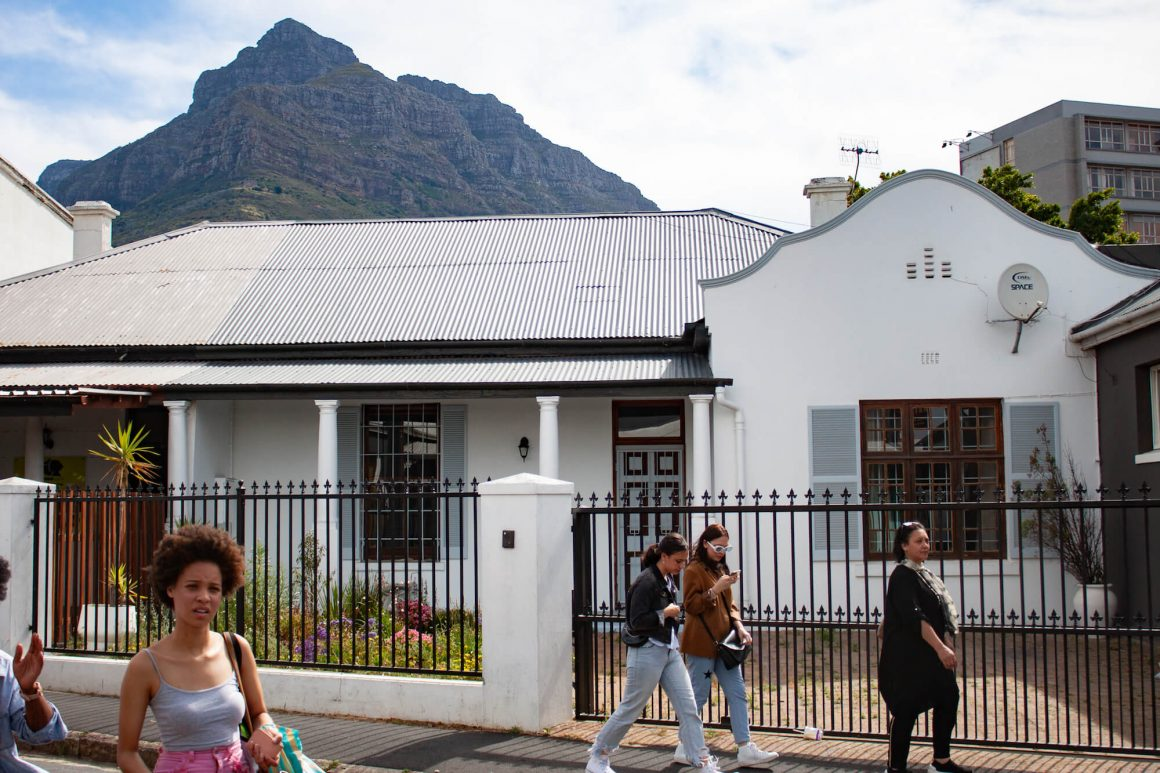 Locals walking around the Observatory neighborhood in Cape Town with Devil's Peak in the background.