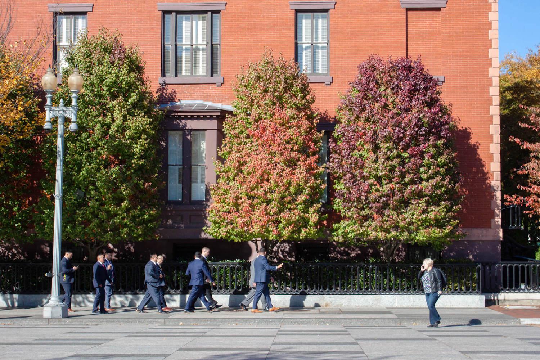 Row of guys in suites walking along D.C. Street