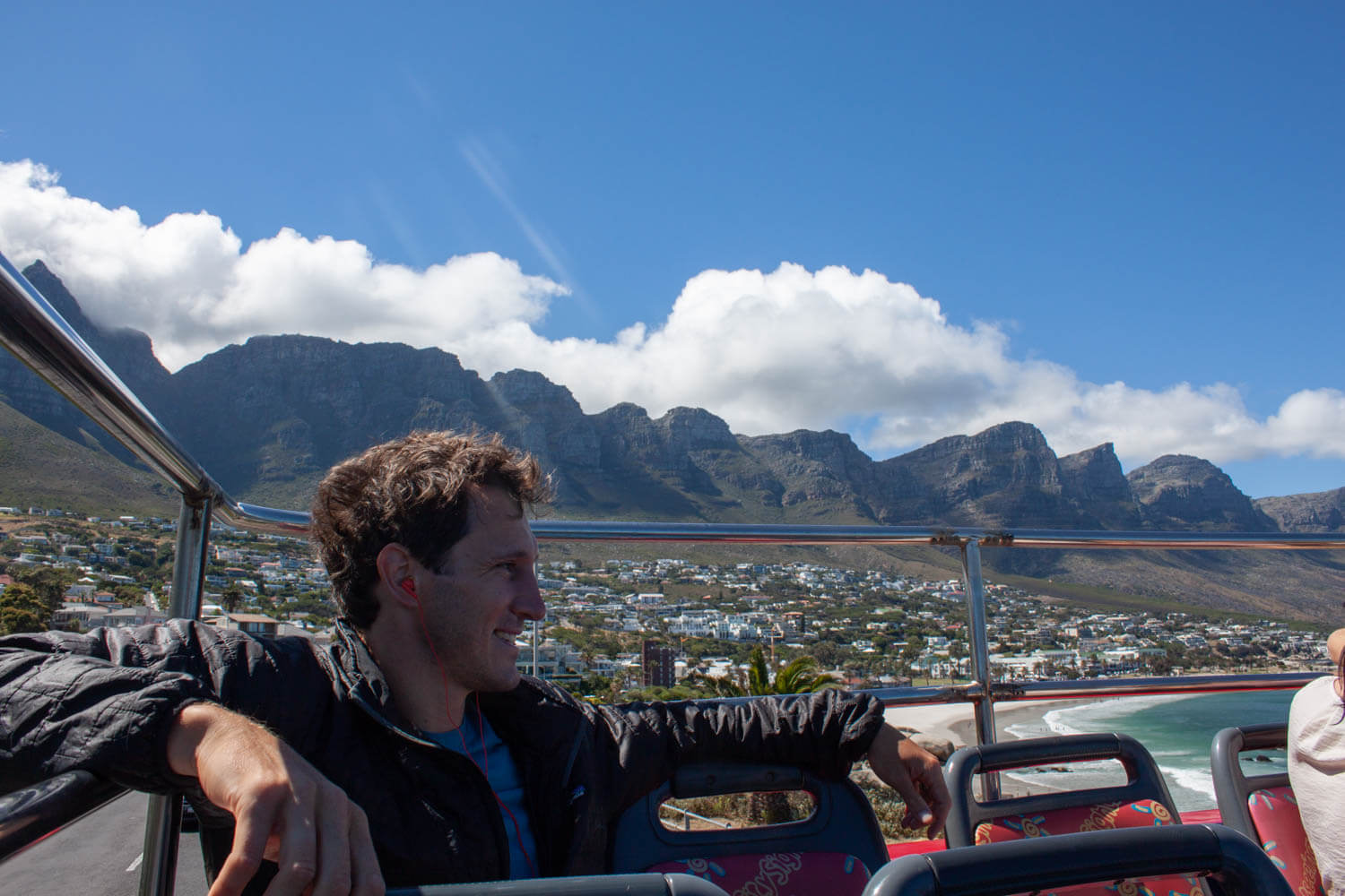 Chris chilling on the back of the hop on hop off bus with the Twelve Apostles in the background