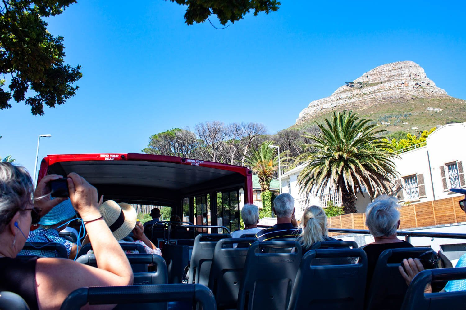 Tourists looking at Lions Head from the hop on hop off bus