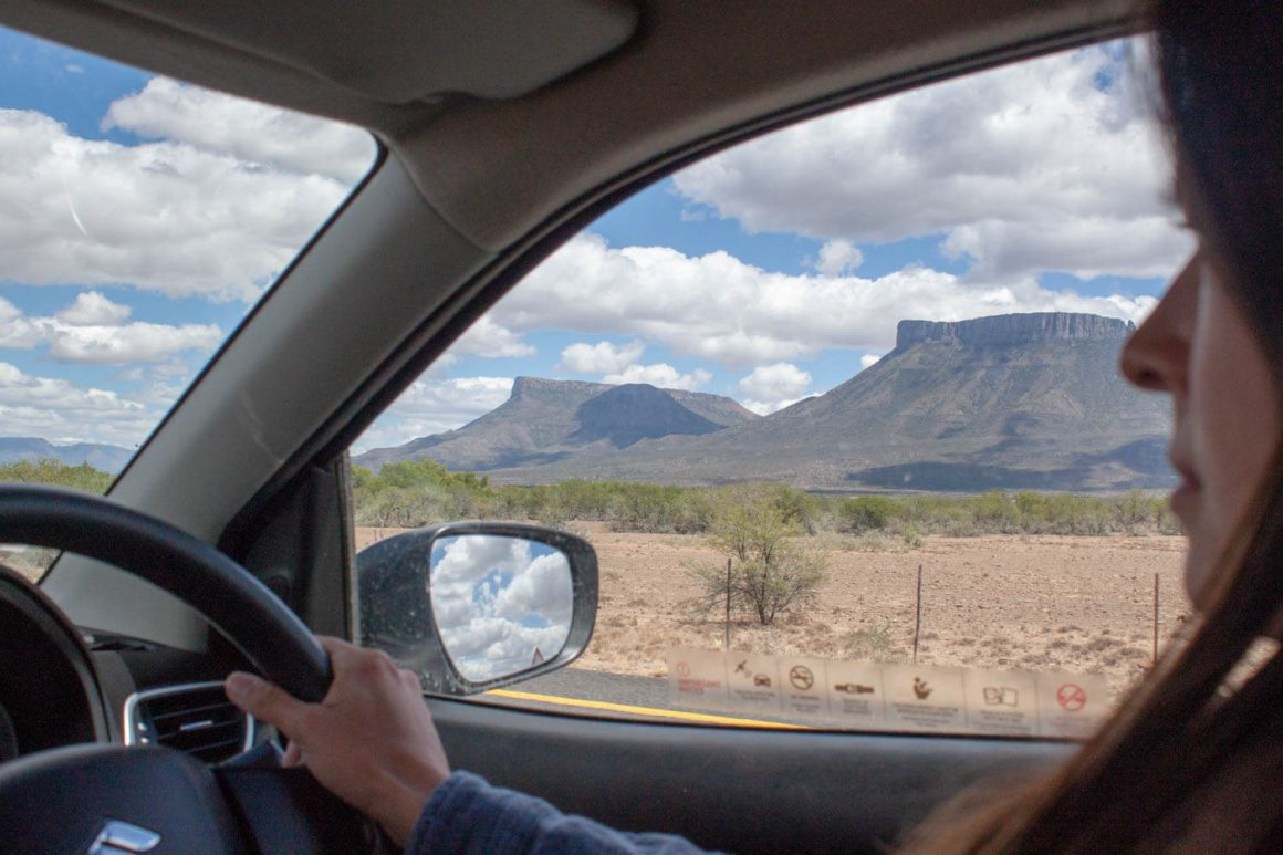 View through driver's side window of mountains, desert, and clouds in rearview mirror