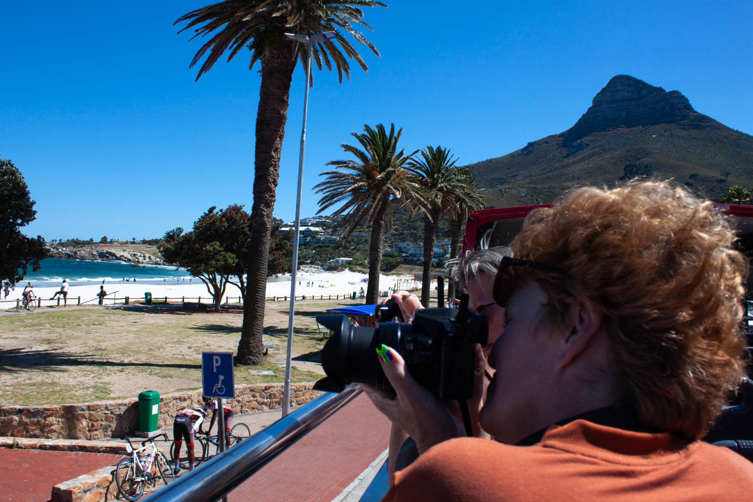 Lady taking photo of Camps Bay with Lions Head in background