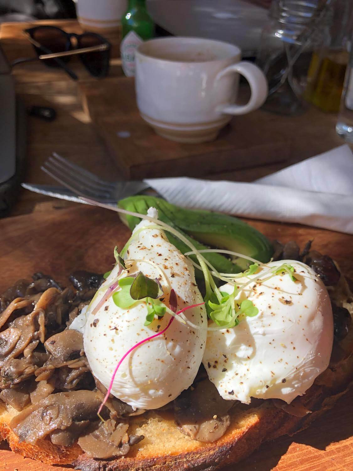 Close up of mushroom, poached egg, avocado toast from The Stranger's Club.