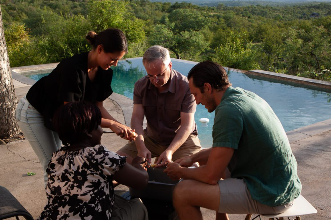 Chris, Kim, Kim's dad, and Selina making marula wine.