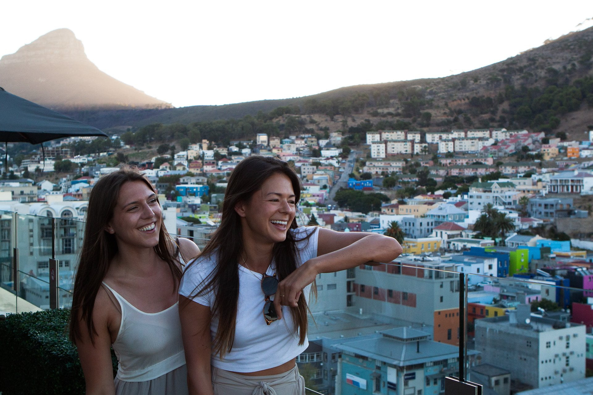 Cape Town travel tips - Marina and Kim on a rooftop in CBD with Lions Head in the background