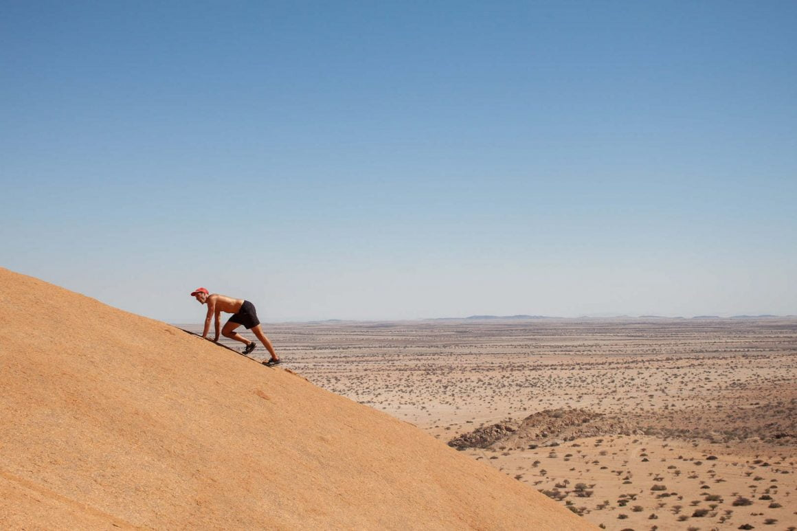 Chris climbs up one of the mountains on all fours in Spitzkoppe, Namibia.
