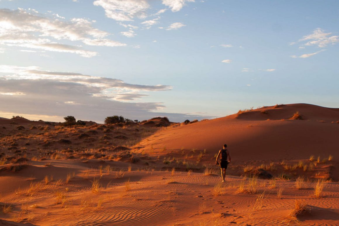 Is visiting Namibia worth it cover image of Chris walking in dune sunset