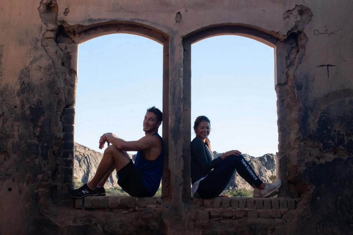 Chris and Kim sitting in an abandoned house by Goanikontes in Swakopmund