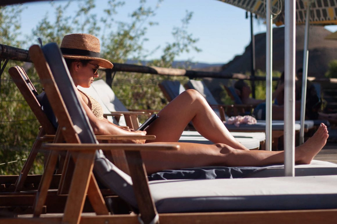 Kim relaxing and reading her book by the pool at Felix Unite, in Orange River in Namibia.