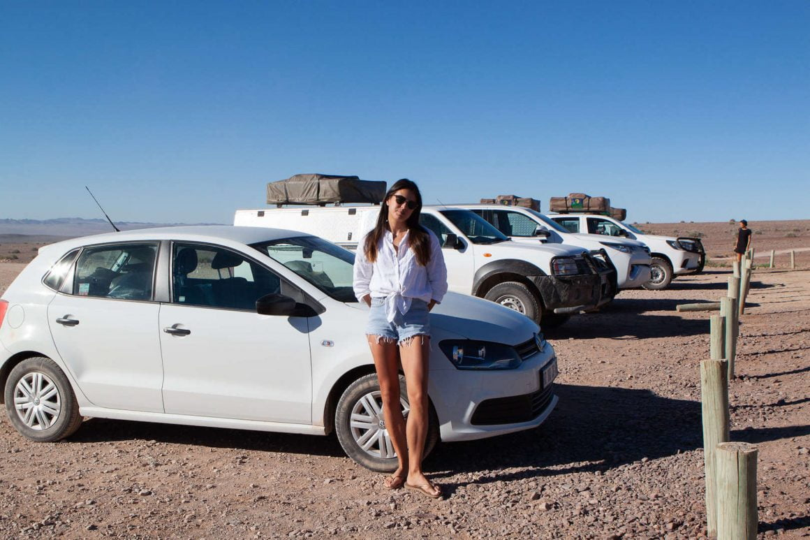Kim stands beside a lineup of 4x4 camping vehicles in a parking lot in Fish River Canyon