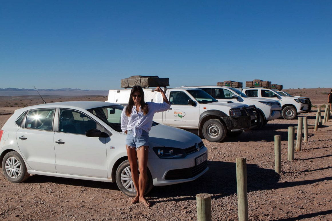 Kim showing us her guns beside the other camping 4x4s and our tiny Volkswagen Polo in a parking lot in Fish River Canyon