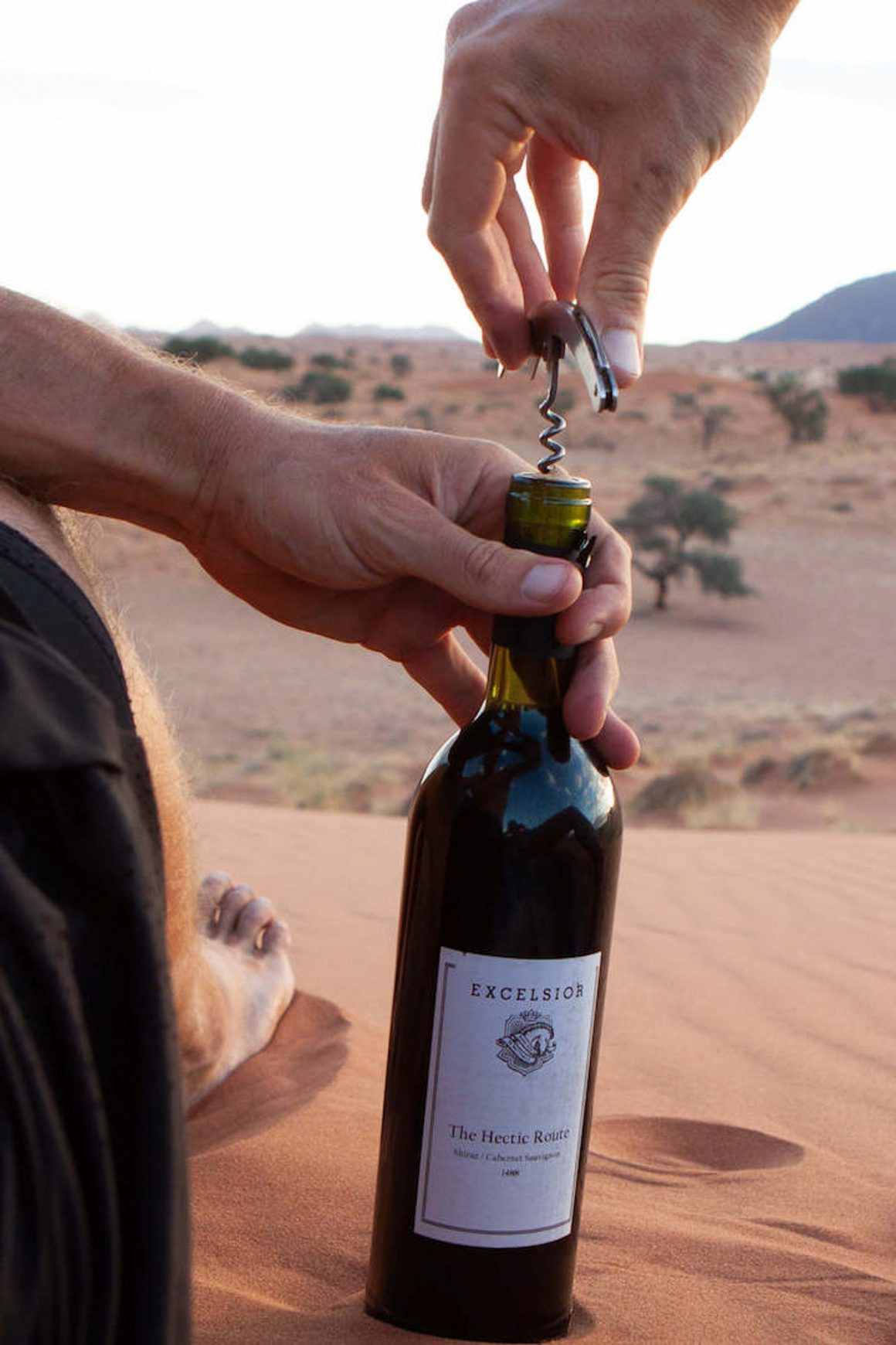 Chris opening a bottle of our Hectic Route wine on a sand dune near our campsite in Namibrand, Namibia.
