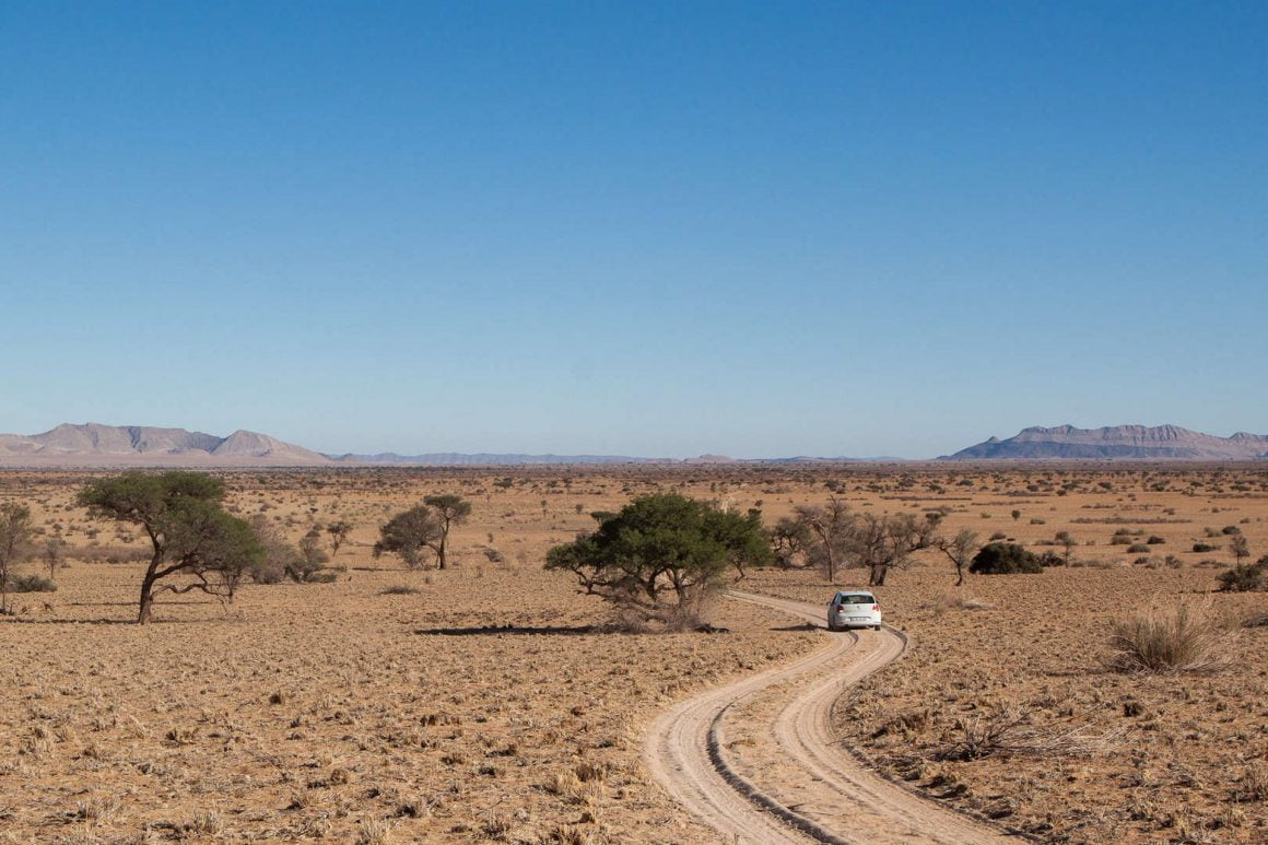 Our VW polo drives along an empty dirt and sand road by Gecko Camp