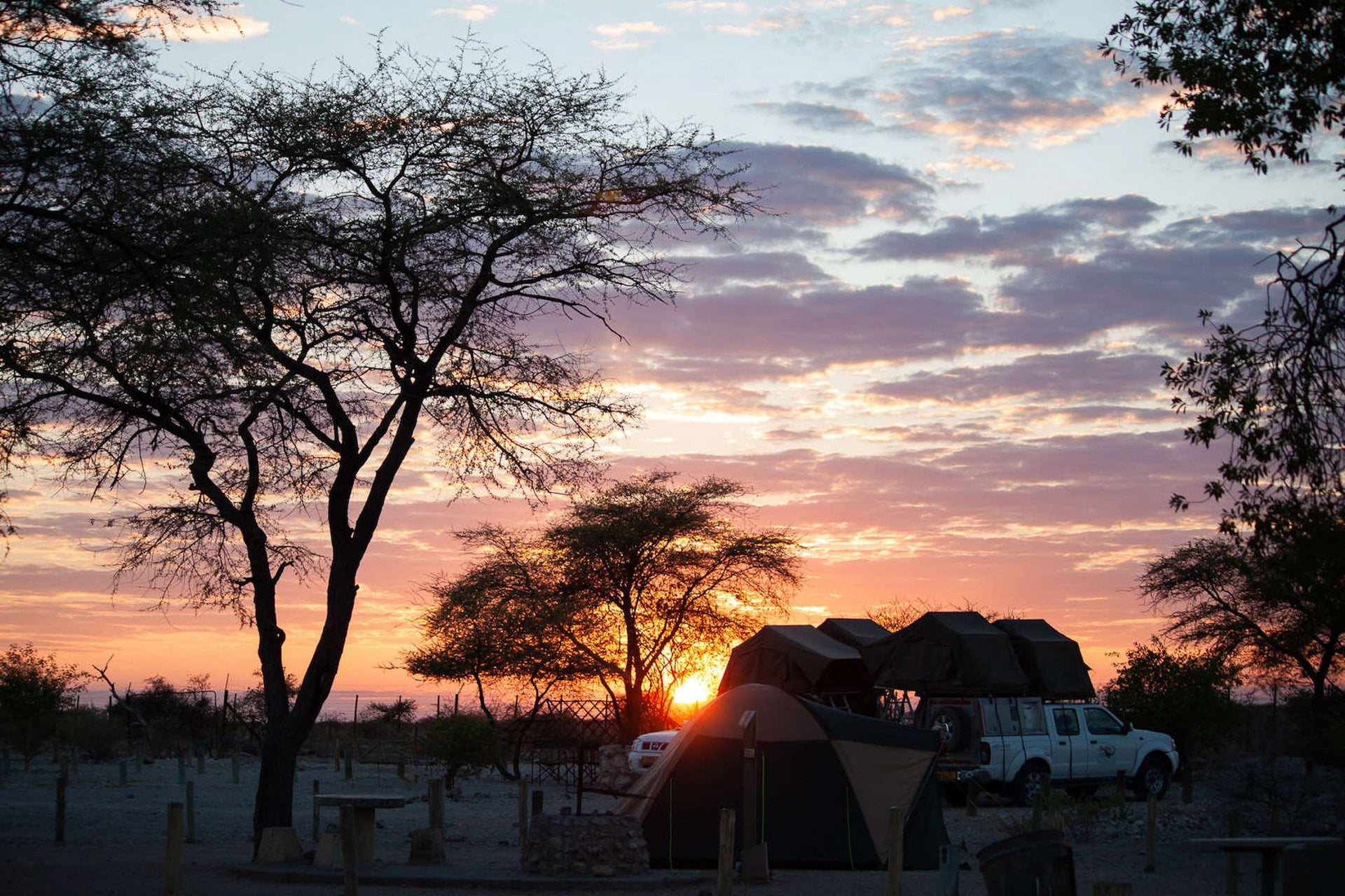Cape Town to Namibia Road Trip cover photo - unrise at Okaukuejo Camp in Etosha with camper trucks in the foreground.