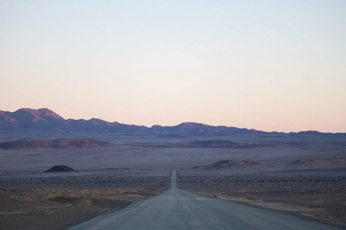 A straight gravel road at sunrise towards Fish River Canyon