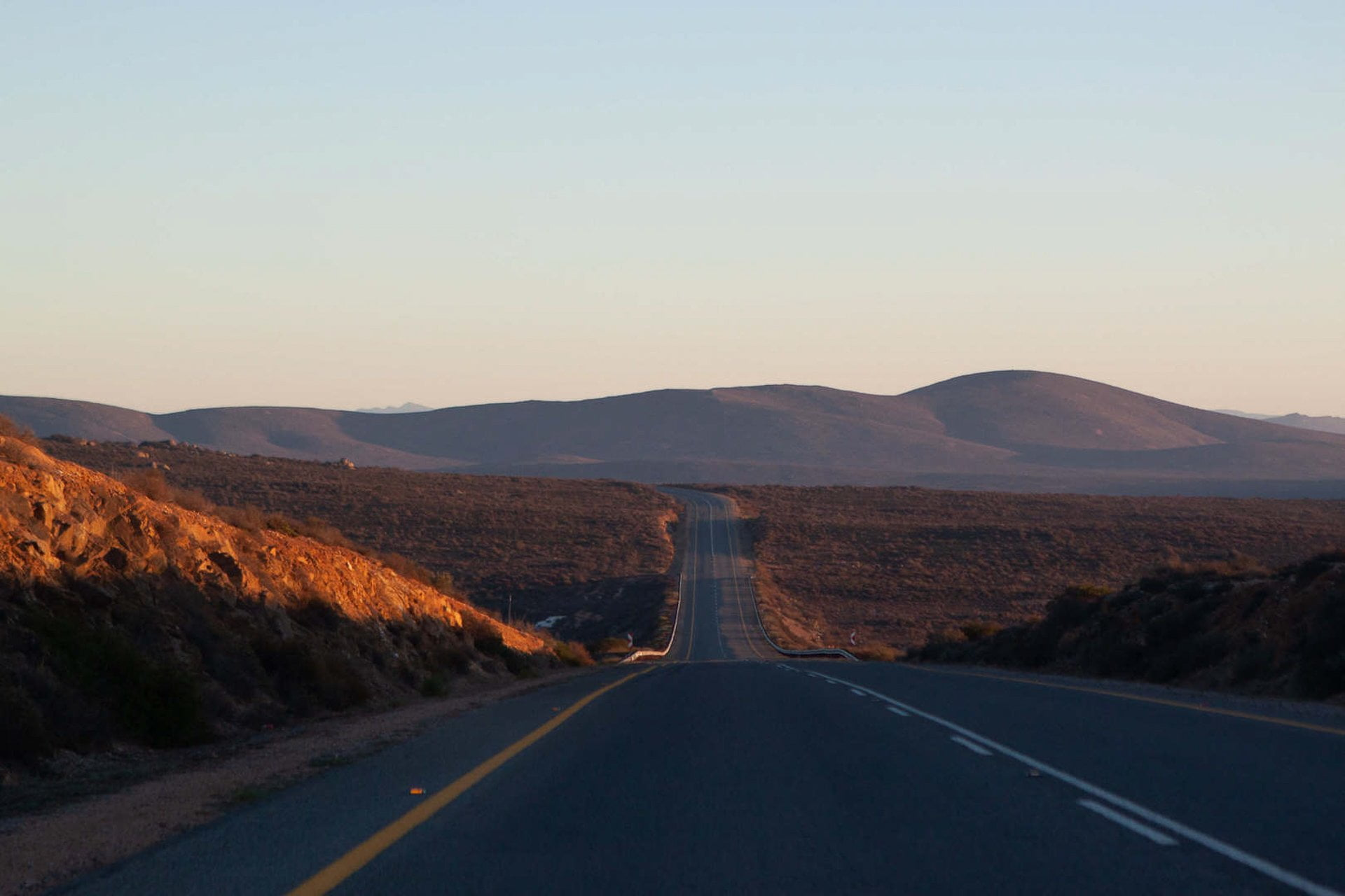 South Africa Road trip tips cover of sunrise view of highway driving towards the Namibian border.