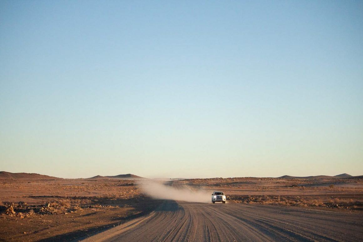 Truck at sunrise speeding across the gravel roads in Fish River Canyon