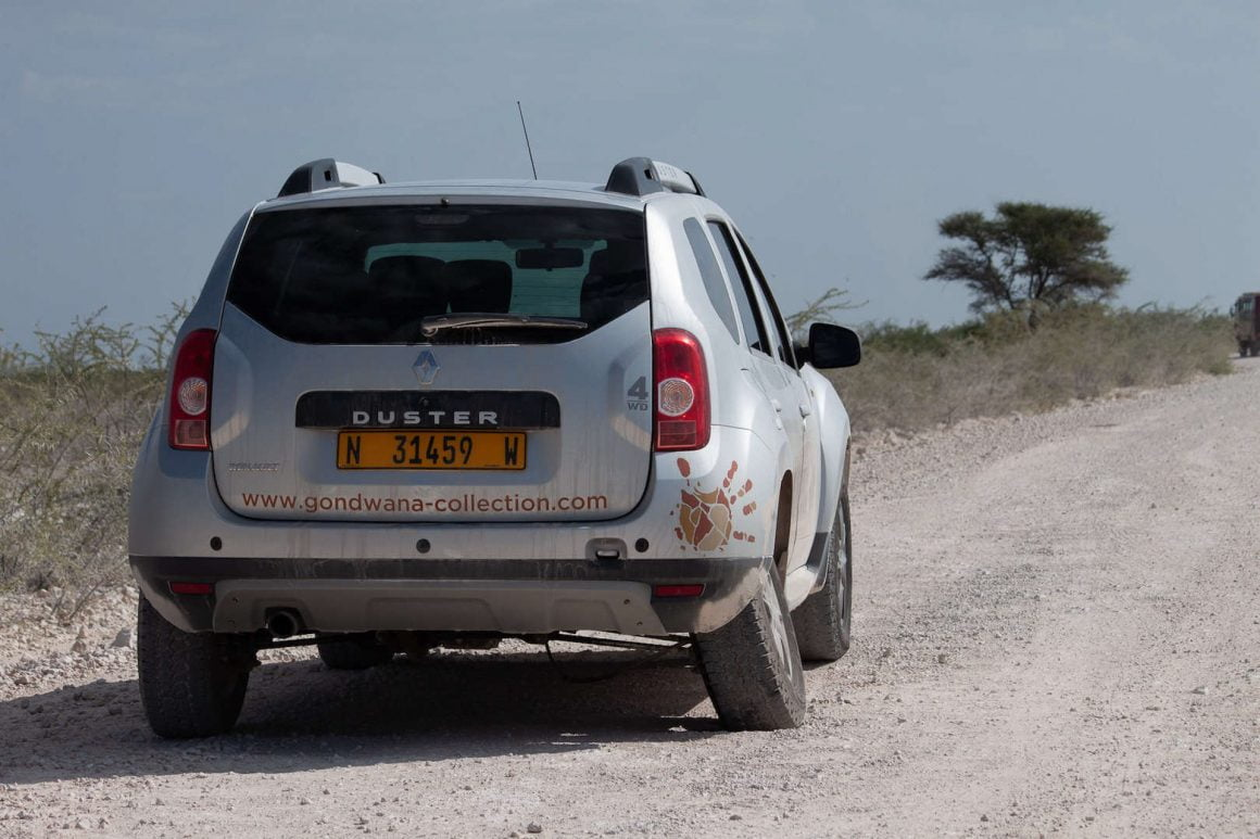 A 4x4 rental car with a flat and broken tire in Etosha, Namibia