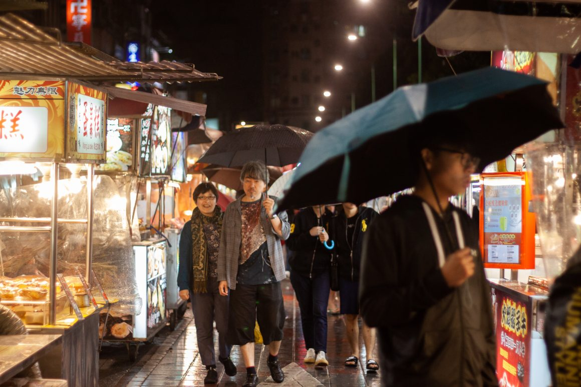 Umbrellas and local Taiwanese people walking the narrow Taipei streets at a local night market