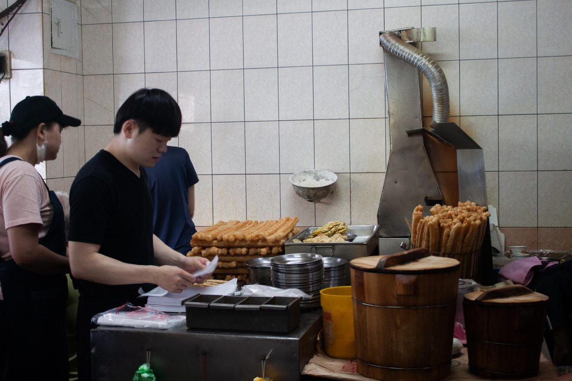 Guy making food at Sihai Soy Milk restaurant in Taipei.