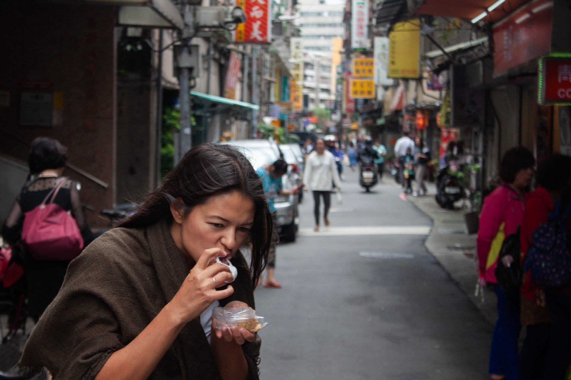 Cover image of Taipei 24 hour layover post. Kim eating on street.