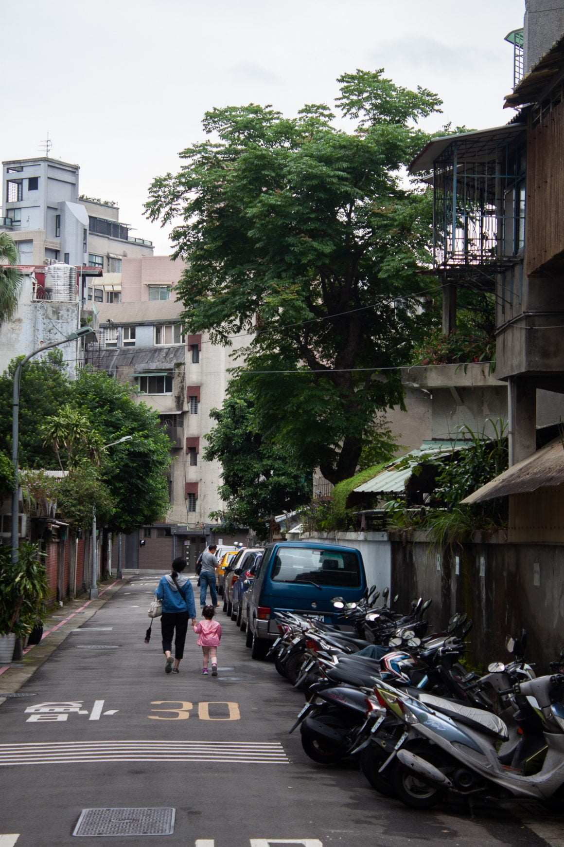 Mother and daughter hold hands walking down a quiet street in Taipei