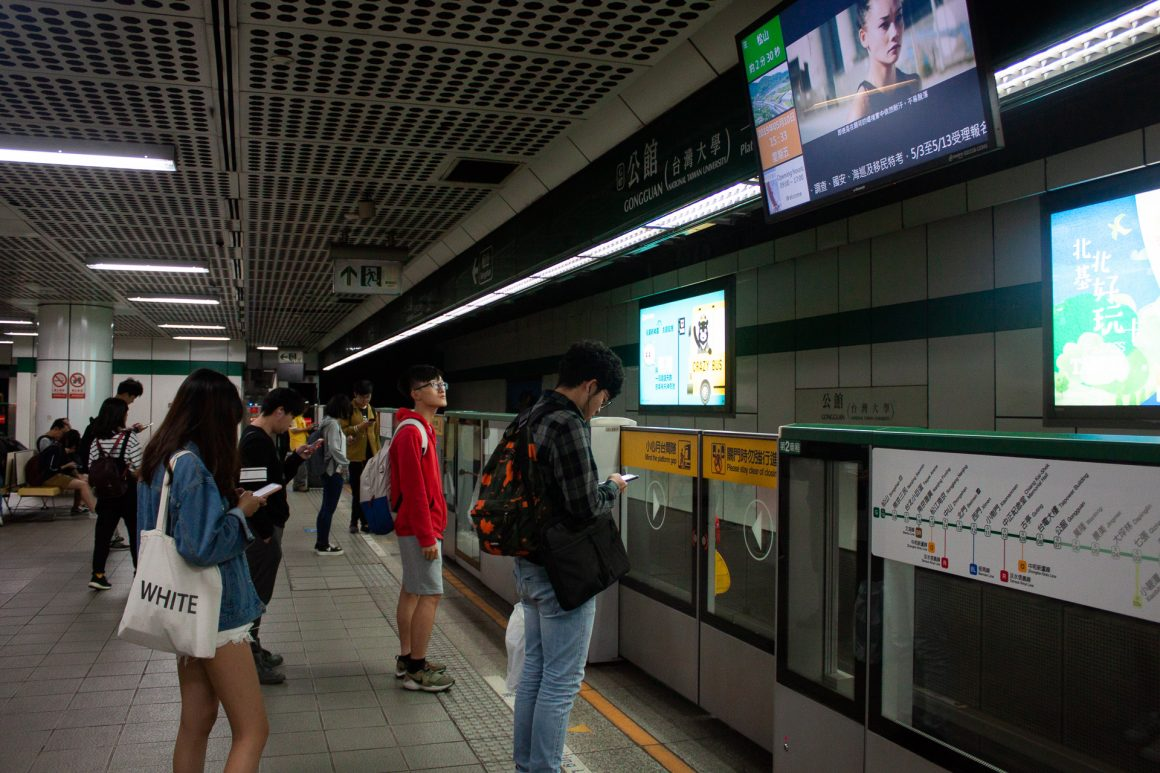 Locals standing and waiting at the MRT subway station