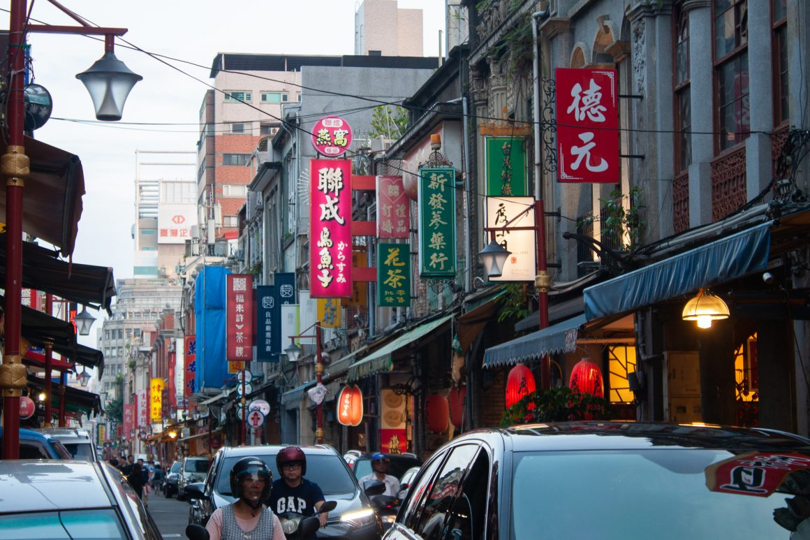 Busy streets with storefronts, cars, and motorcyclists at rush hour in Taipei.