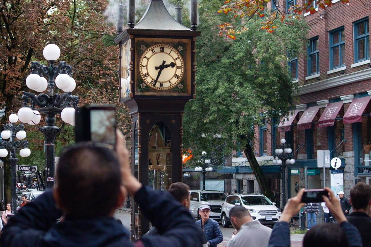 Tourists taking photos of the famous steam clock in Gastown