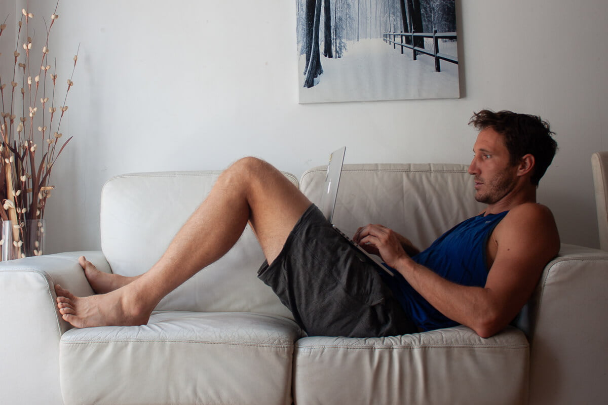 Chris wears his comfortable Icebreaker Momentum shorts while lounging and doing work on the couch.