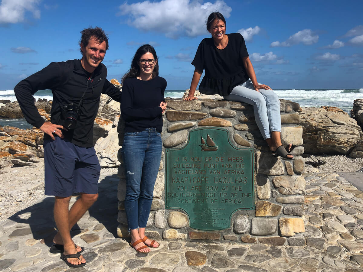 "Group picture of Chris, Rebecca, and Kim standing in front of the ""Southern Most Tip of Africa"" sign at Cape Agulhas"