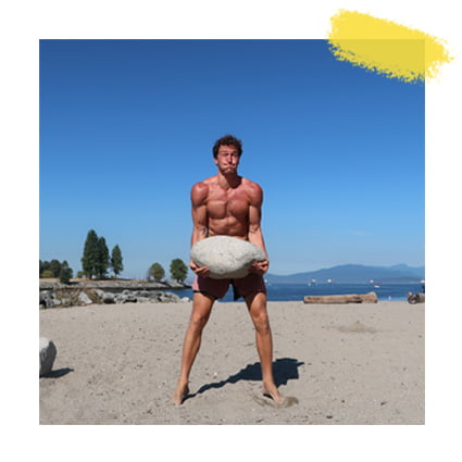 Chris lifts a super heavy rock at the beach during a beach workout in Vancouver, Canada.