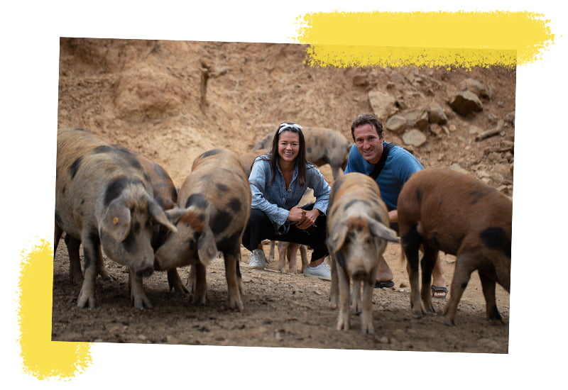 Kim and Chris squatting by the most expensive jamon de iberico pigs in Southern Spain.