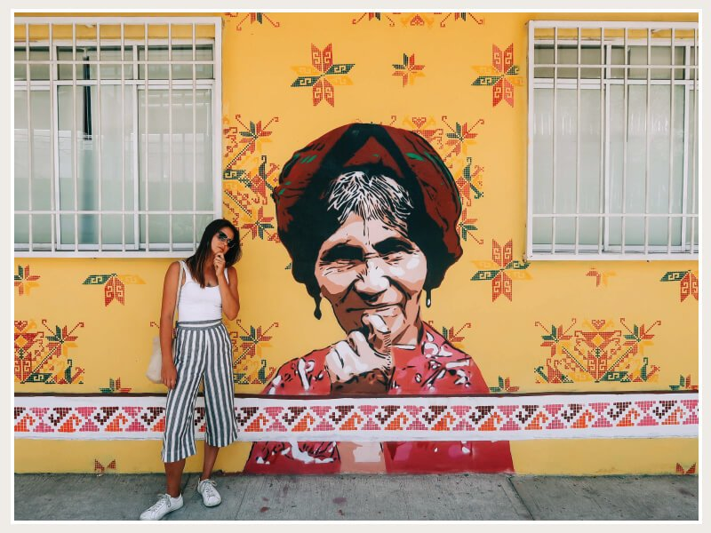 Kim making the same pondering face as the lady in the street art behind her while living in Mexico City.