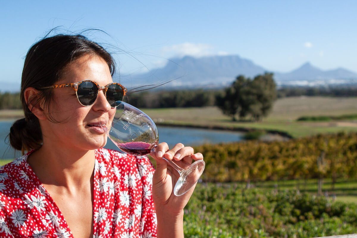 Kim sipping wine outside on a windy patio at De Grendel wine estate, perhaps the best wine tasting in Cape Town.