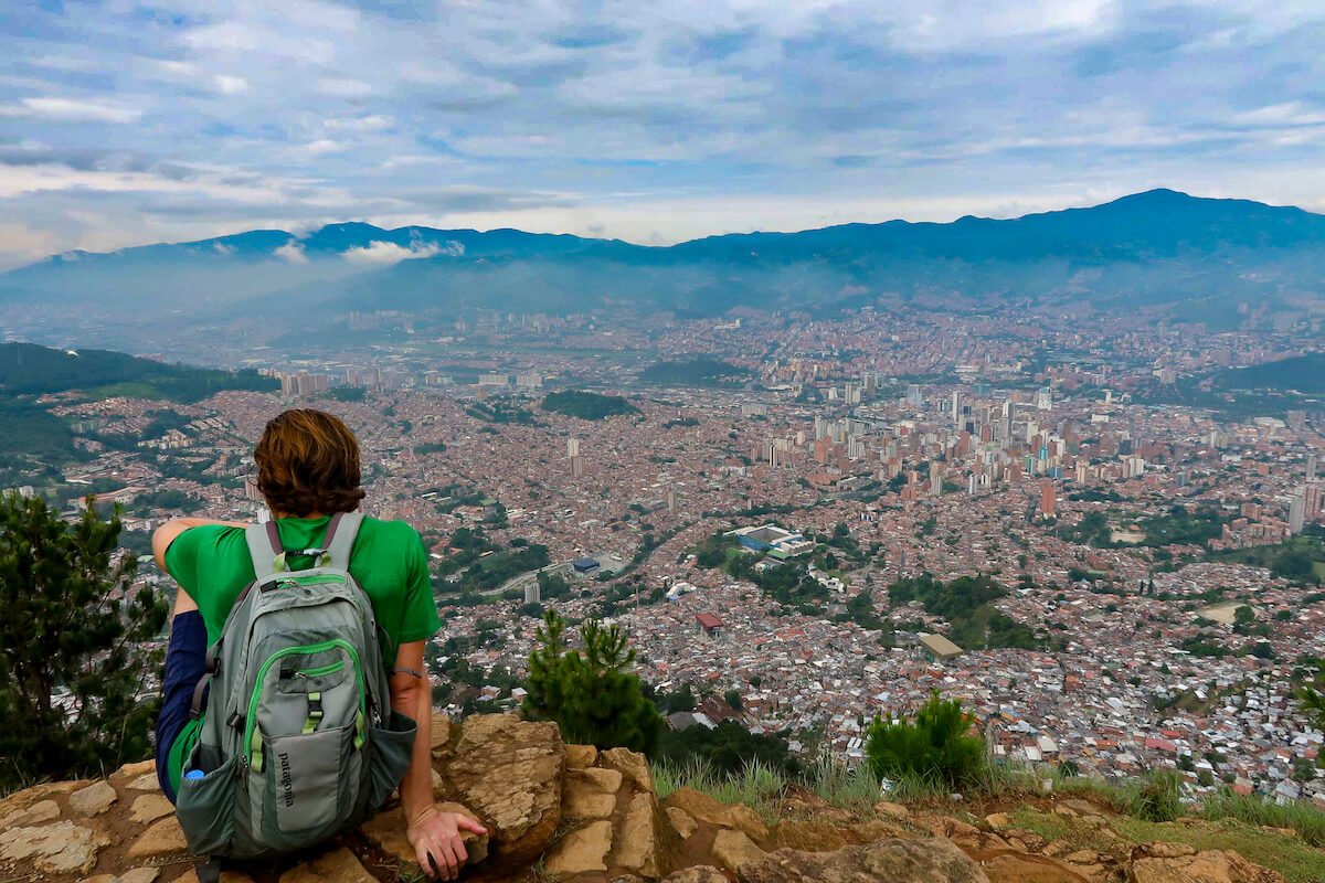 Medellin travel blog cover image of Chris looking out over the city of Medellin