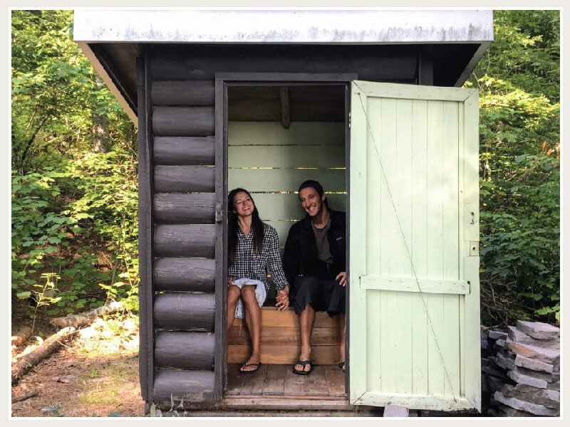 kim and chris together peeing in an outhouse in northern Canada