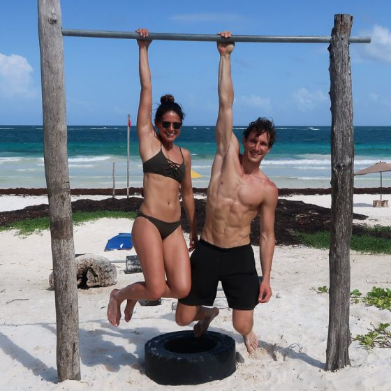 Work out outside cover image of Kim and Chris hanging with one arm on a bar no the beach in Tulum