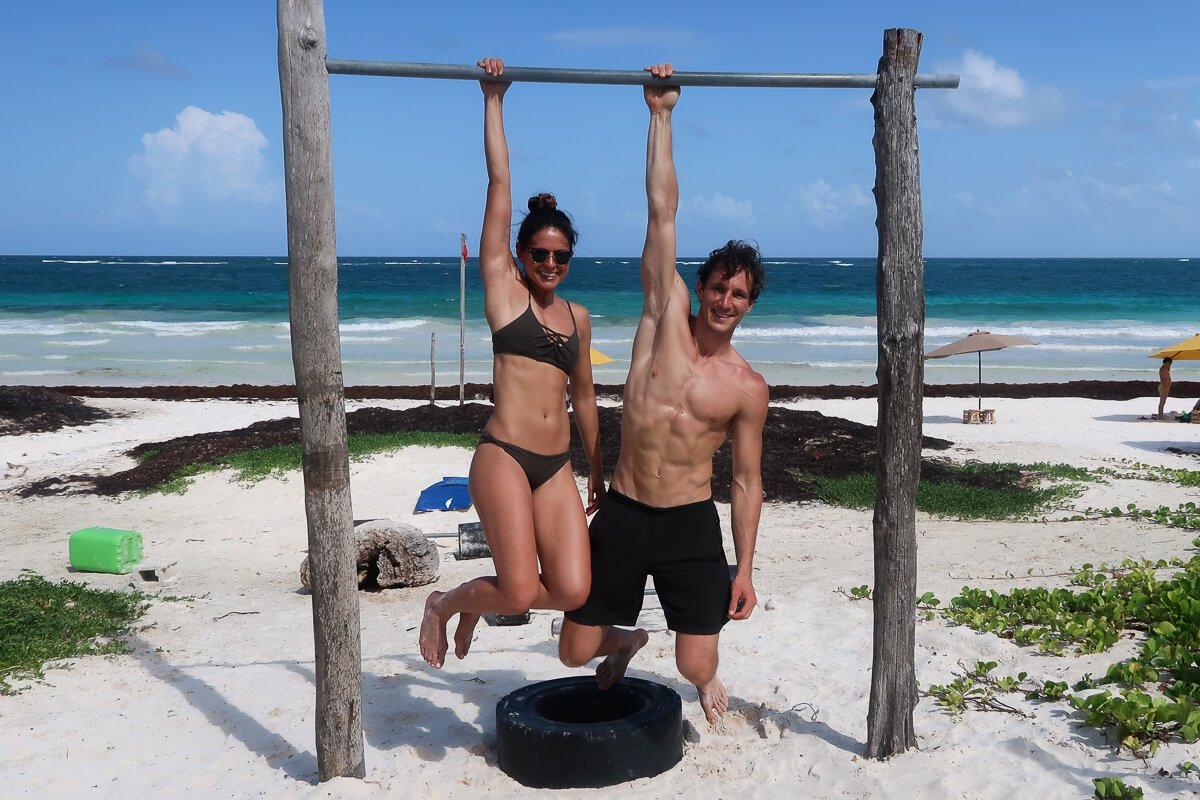 Chris and Kim hanging from a bar on the beach in Tulum